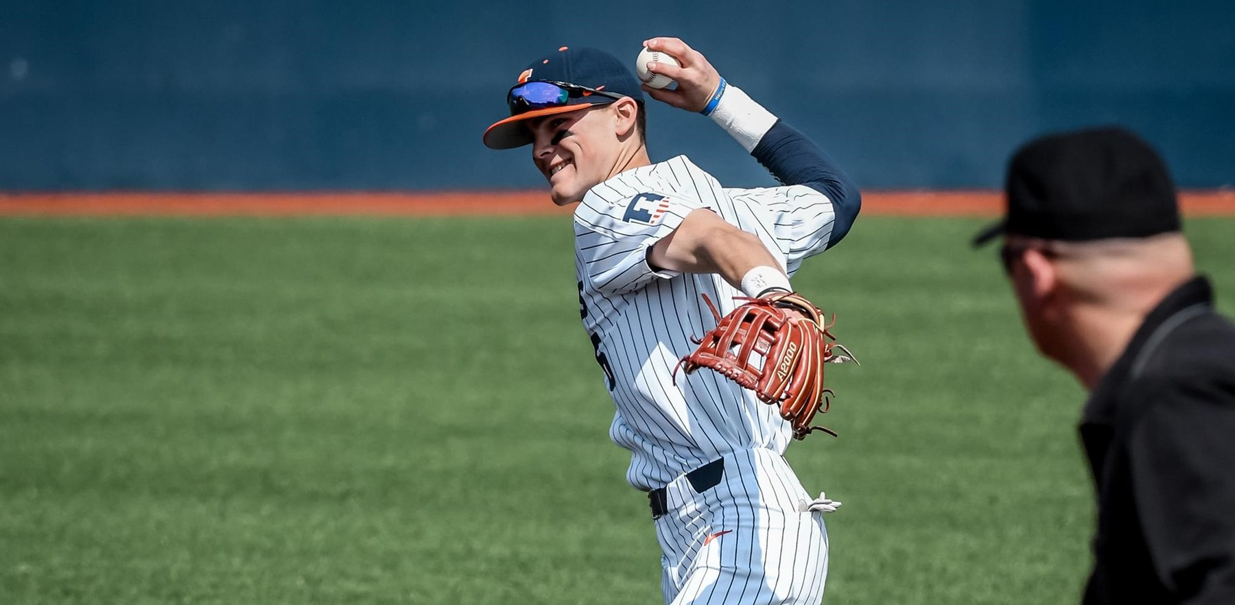 smiling Illini baseball player throws the ball as an umpire watches