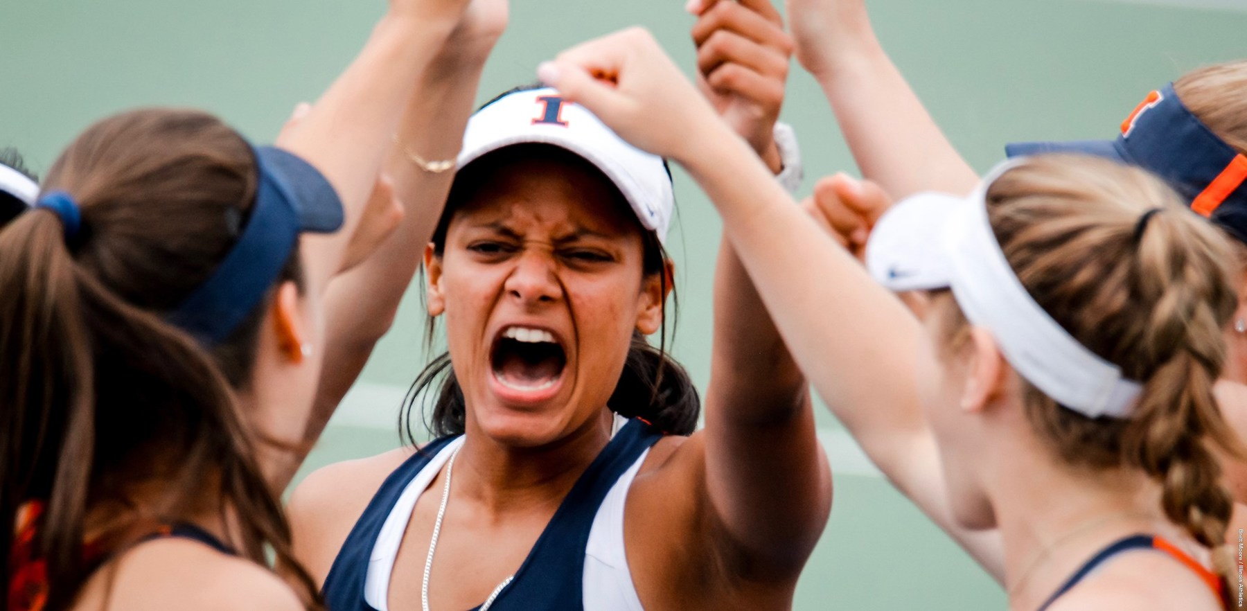 women's tennis player has a fierce expression as she shouts in celebration with teammates.