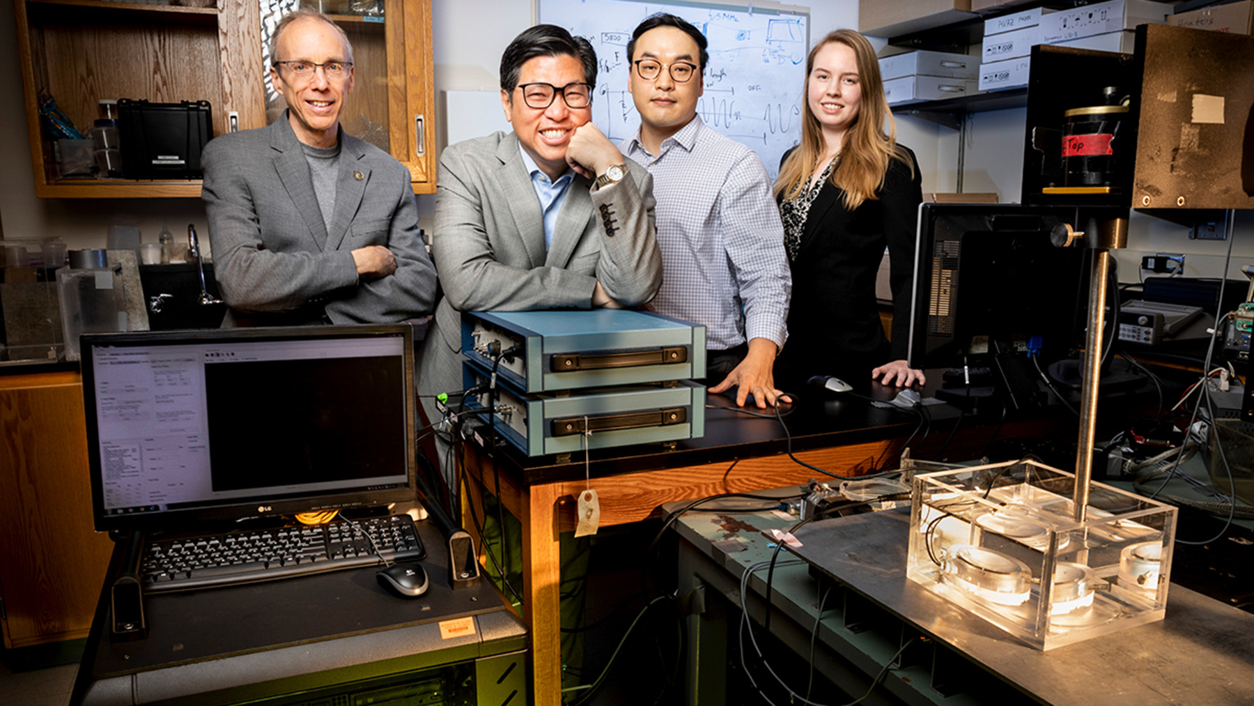Jeffrey Moore, left, King Li, postdoctoral researcher Gun Kim and graduate student Abigail Halmes have collaborated to develop an ultrasound-activated synthetic molecule that can emit light deep inside biologic tissue for a variety of medical uses and therapies.  Photo by Fred Zwicky