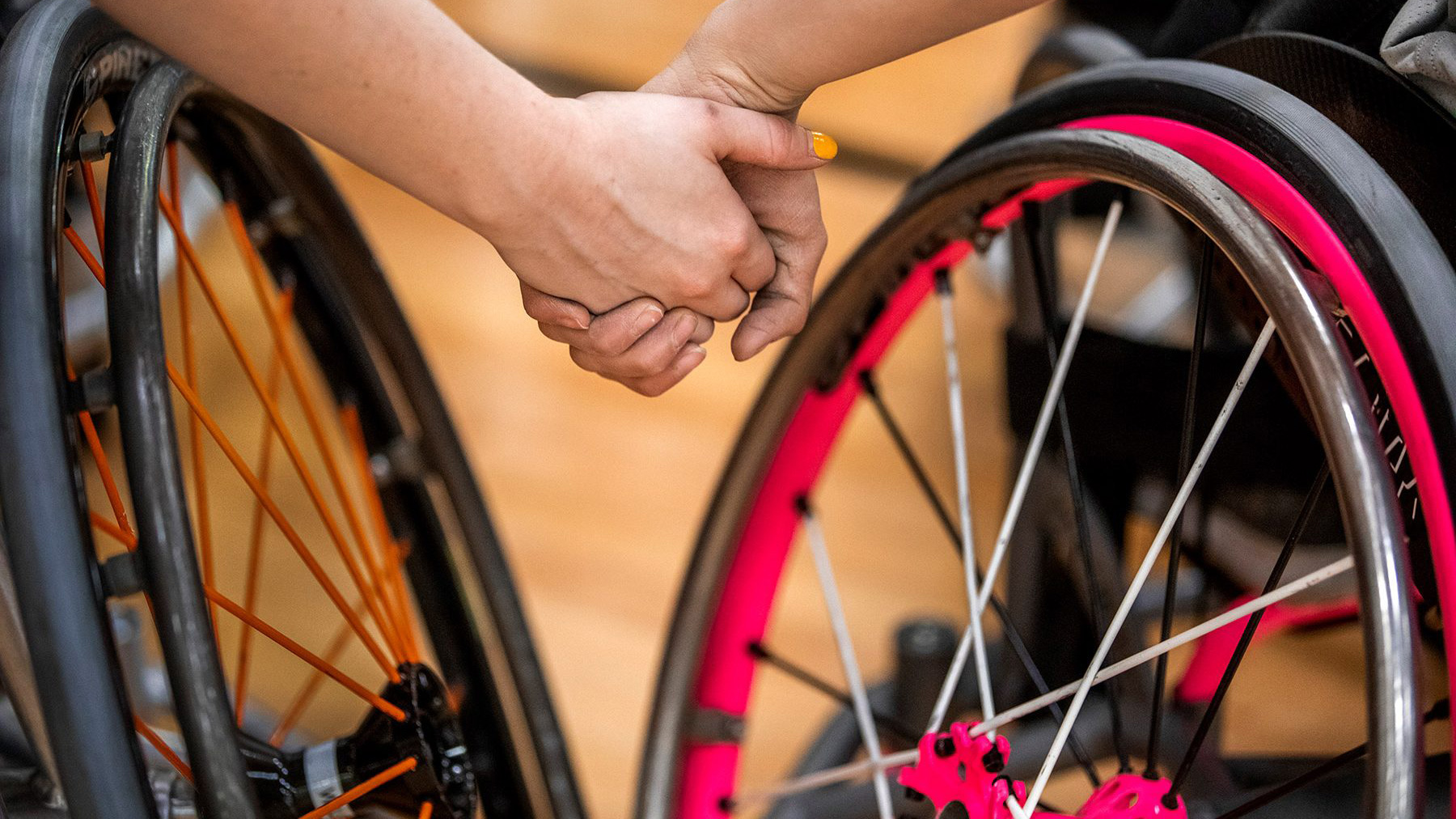 wheelchair athletes holding hands - closeup of hands and chairs' wheels. Photo by Fred Zwicky.