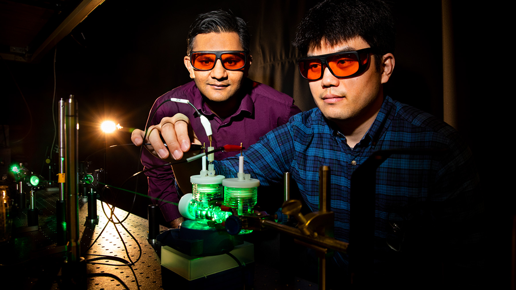 Professor Prashant Jain and doctoral student postdoctoral researcher Sungju Yu performing artificial photosynthesis experiments using green light.  Photo by Fred Zwicky