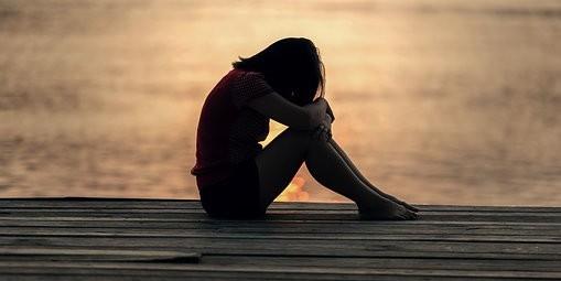 silhouettte of woman sitting on dock, head on knees