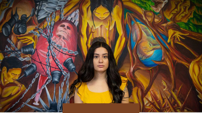 Carolina Kuhl in front of the murals from La Casa Cultural Latina