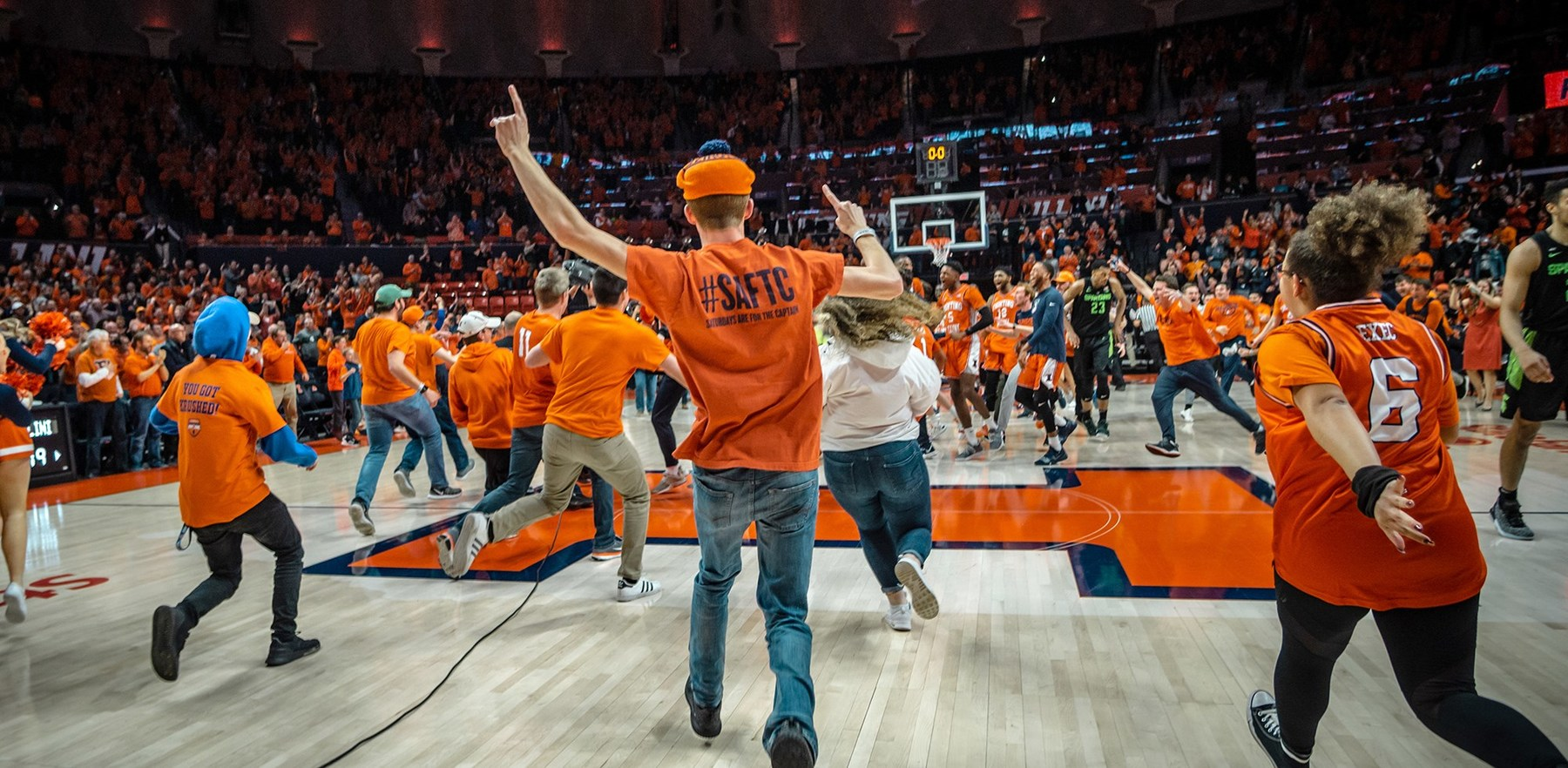 Students flood the floor of Lou Henson court in the State Farm Center
