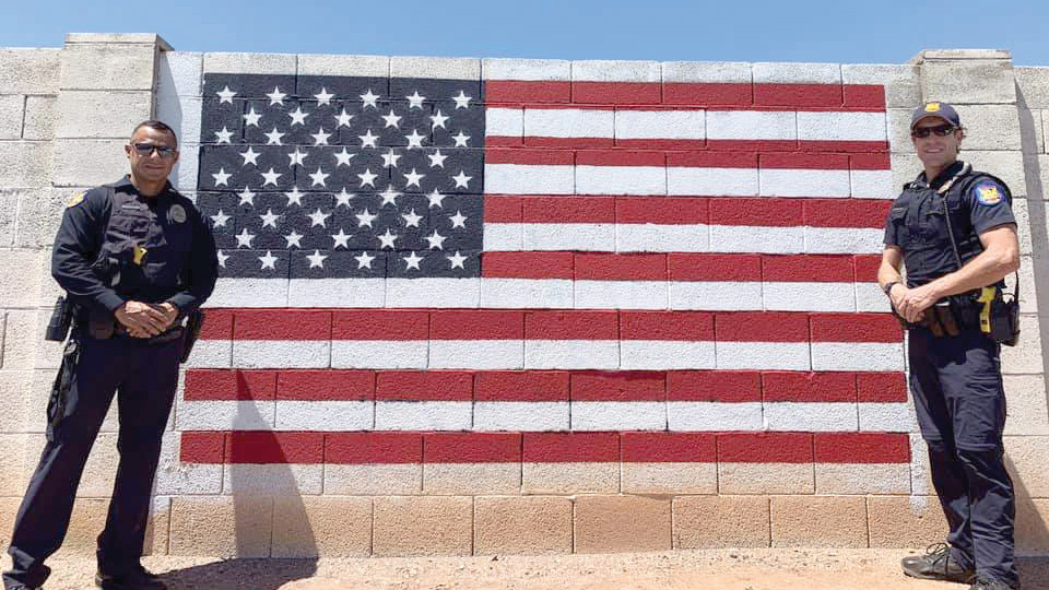 Phoenix police officer aside an American flag painted on cement block wall.  photo courtesy Fallen Heroes Wreath Program Arizona]