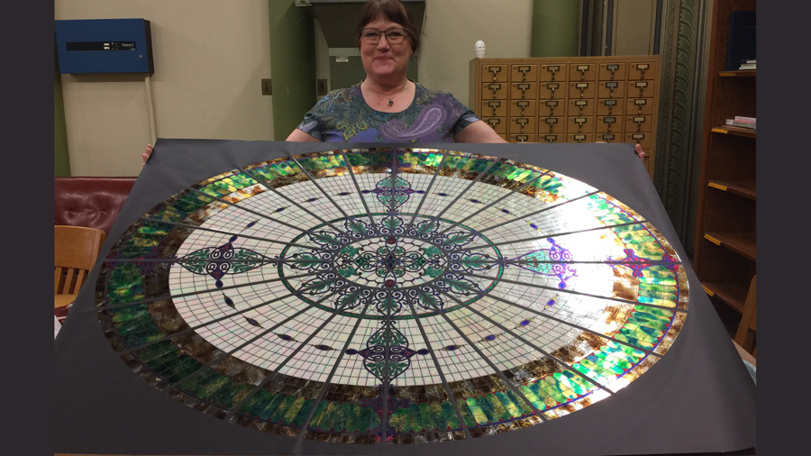 Jane Bergman displays her replica of the glass dome that once overlooked the library in Altgeld Hall. (Photo courtesy of Jane Bergman.)