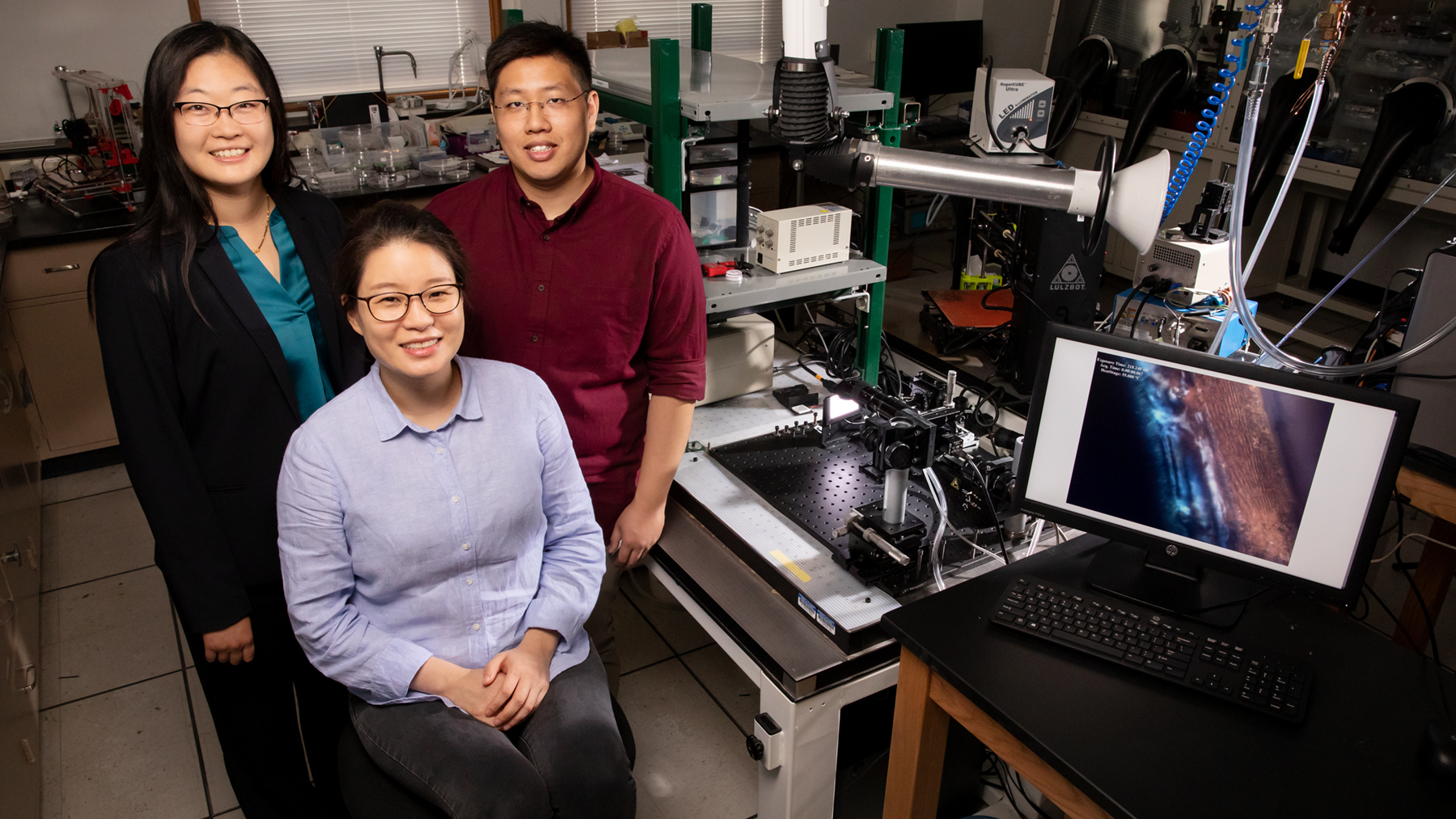 Professor Ying Diao, left, postdoctoral researcher Kyung Sun Park, seated, and graduate student Justin Kwok have found that twisted polymers can be flattened via the printing process to make them better at conducting electricity. Photo by Leslie B. Stauffer