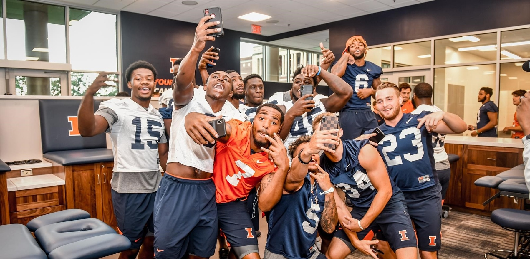football players goofing for camera in new football facility