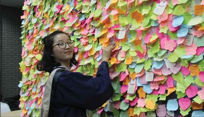 YingYing Zhang at a board covered with post-it notes