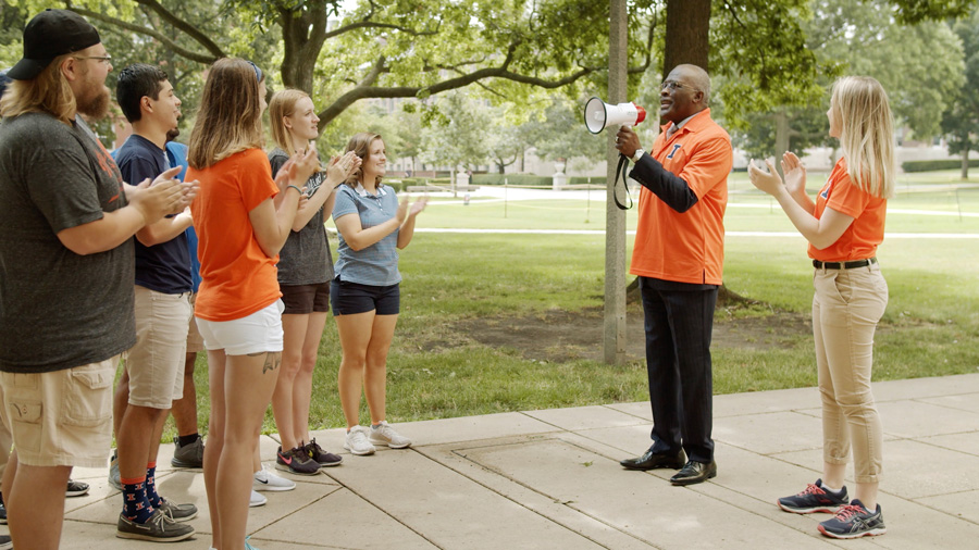 still image of Chancellor Jones leading a group of students on a tour.