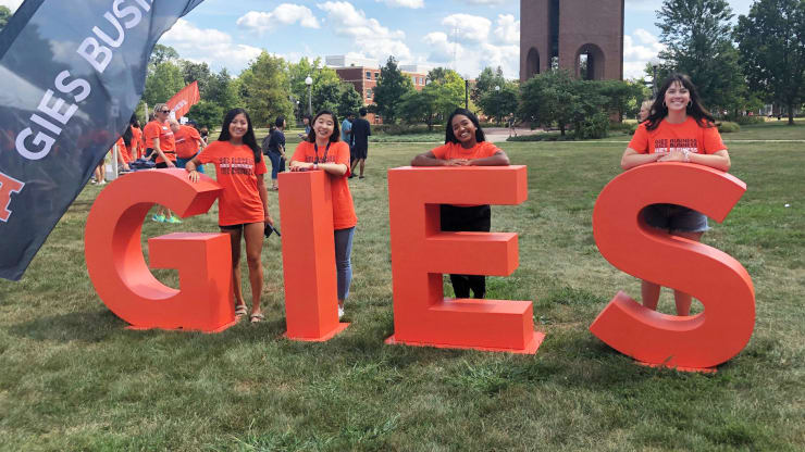 students stand at sign for Gies College of Business at Illinois