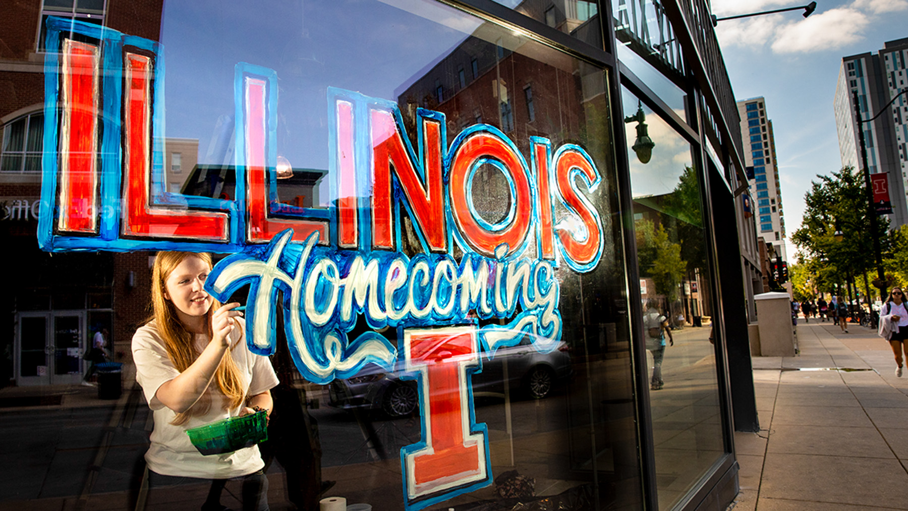 Illinois art student Natalie Bready creates a mural on a Campustown business's window.  Photo by Fred Zwicky
