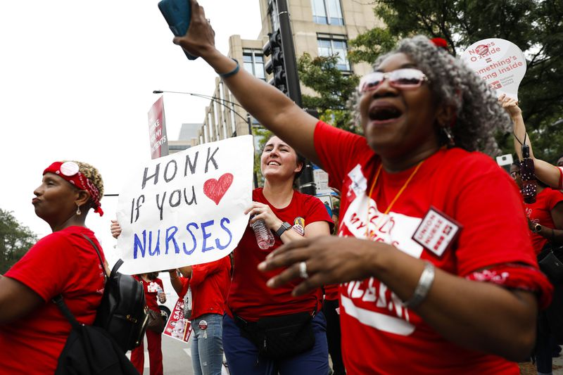 Betsy Overland, center, holds a sign as vehicles drive by and honk as she and other registered nurses chant near the University of Chicago Medical Center where nurses held a one-day strike in Chicago on Sept. 20, 2019. (Jose M. Osorio / Chicago Tribune)