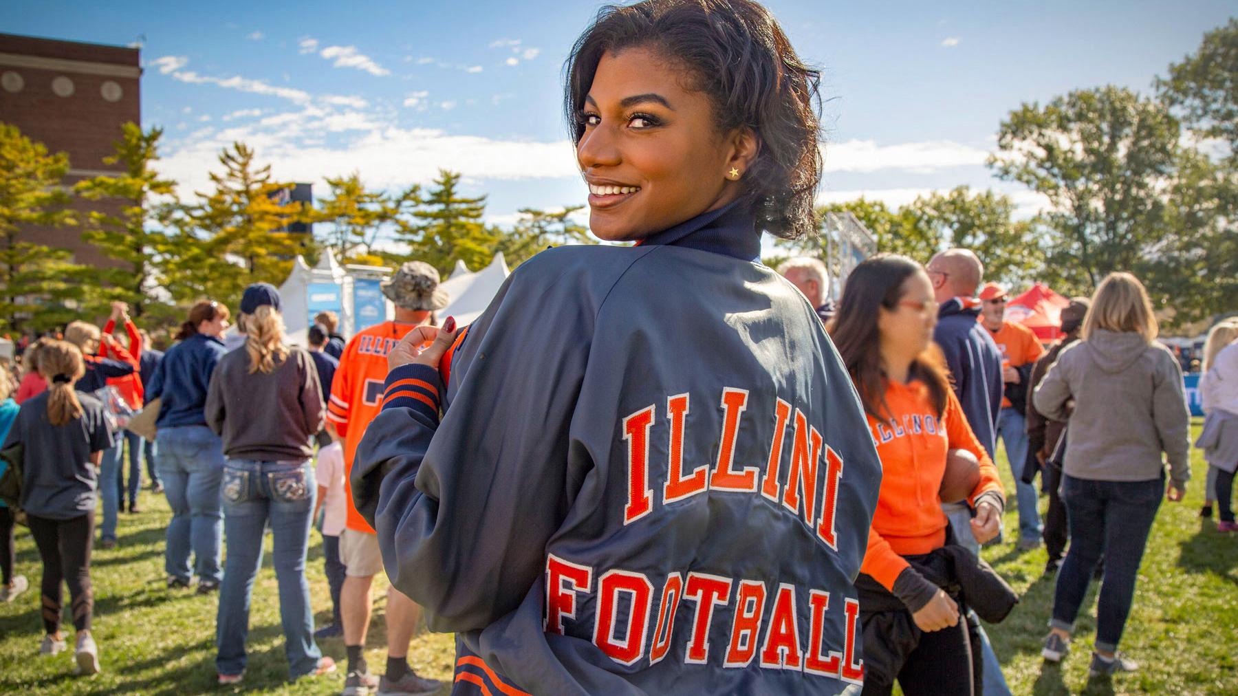 Taylor Rooks, wearing an Illini Football jacket, outside Memorial Stadium