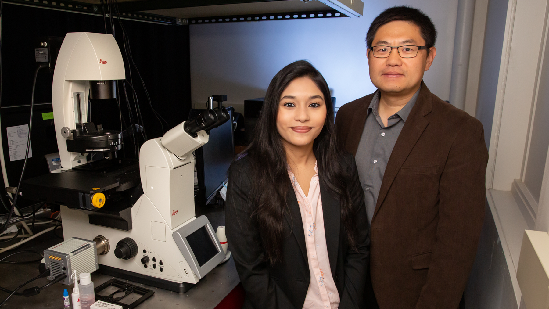 Graduate student Payel Mondal, left, biochemistry professor Kai Zhang and their colleagues developed a new optogenetic technique that will help scientists study protein function.   Photo by L. Brian Stauffer