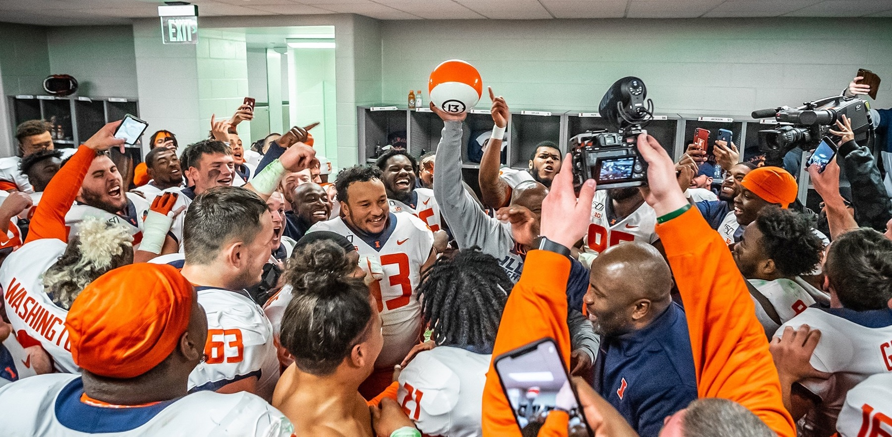 Coach Smith and team celebrate in the locker room following Saturday's win. Smith holds up an orange and white  bowling ball