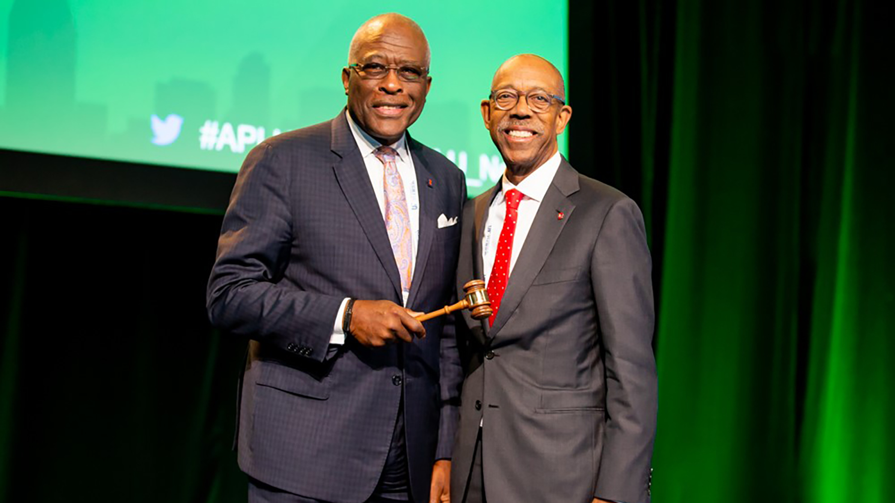 gavel is passed from Michael Drake, President of The Ohio State University and Past-Chair of the APLU Board