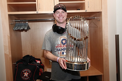 Dan O'Neill ('99, Communications) poses with the World Series trophy in 2017, after the Houston Astros defeated the Los Angeles Dodgers. (Photo courtesy of the Houston Astros.)