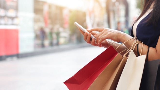 woman with shopping bags working her cell phone. Stock image from Getty Images