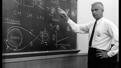 John Houbolt stands in front of chalk board explanation of Lunar-Orbit Rendezvous