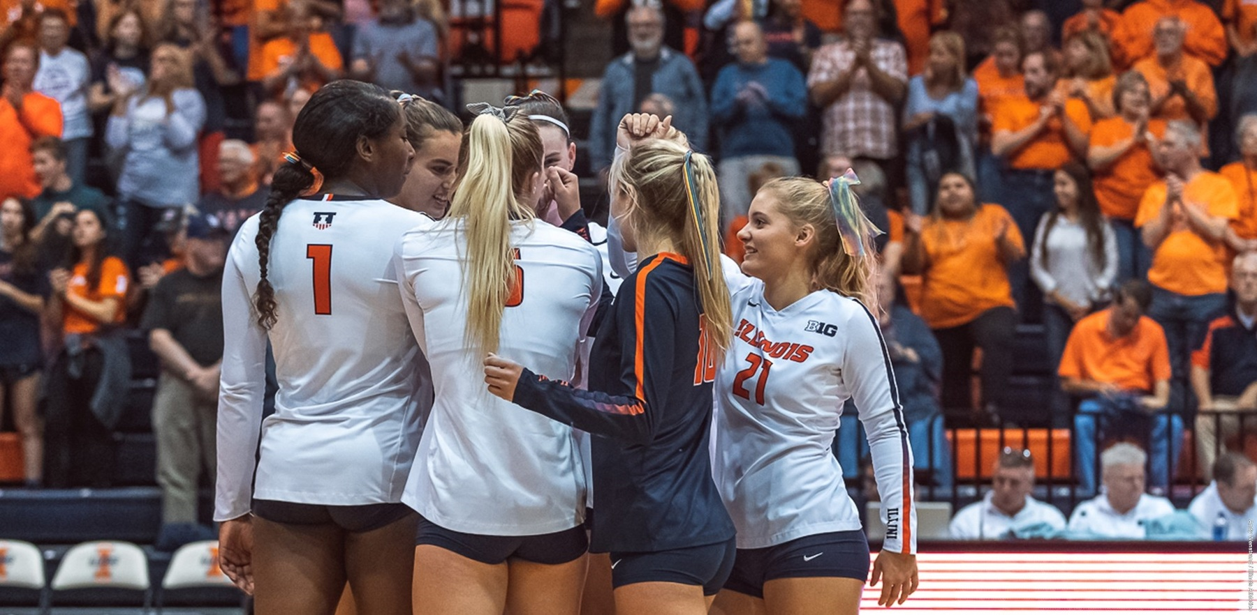 Illini volleyball players huddle on court