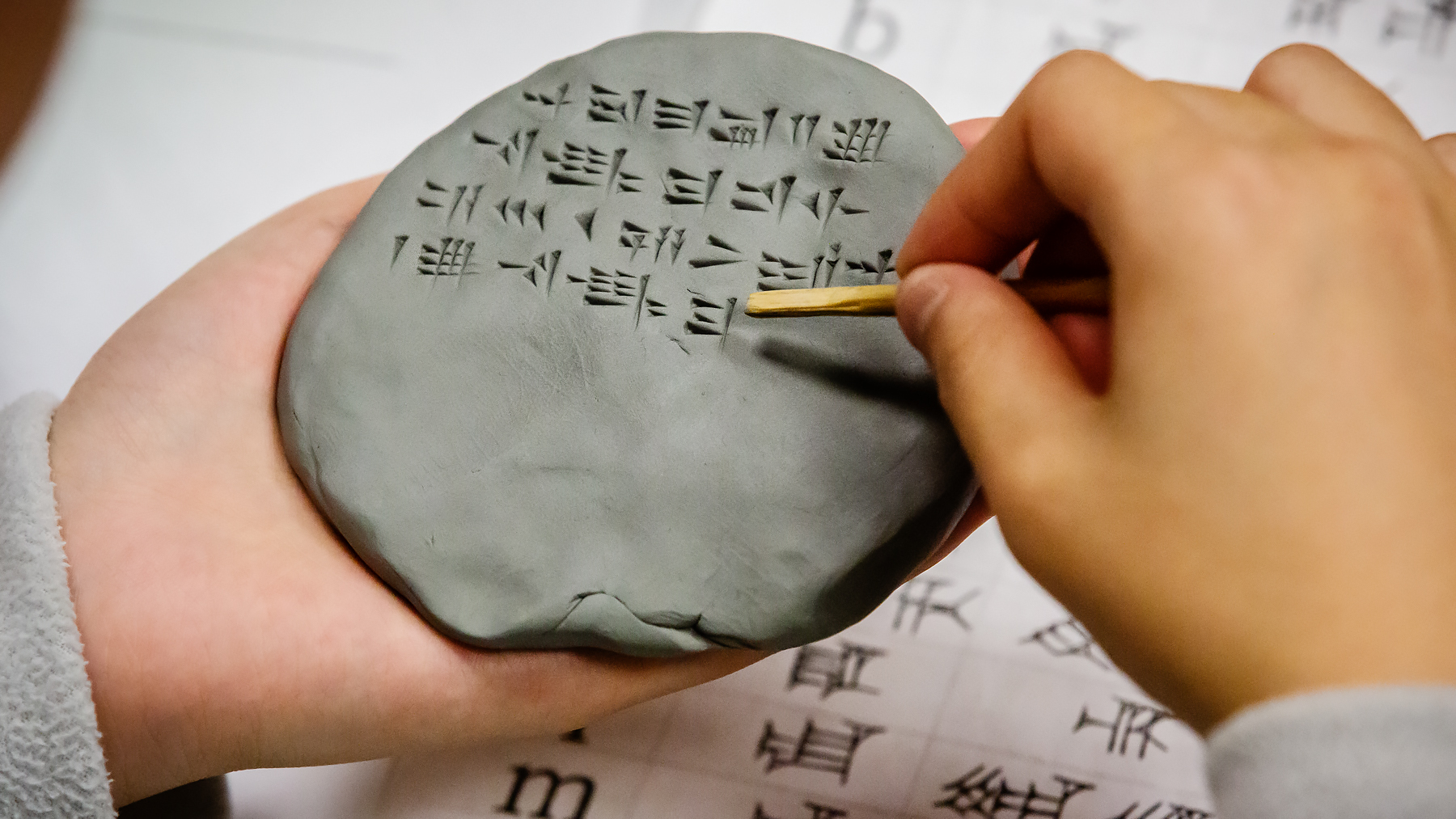 A student writes in Hittite using cuneiform symbols pressed into clay. Photo by L. B. Stauffer