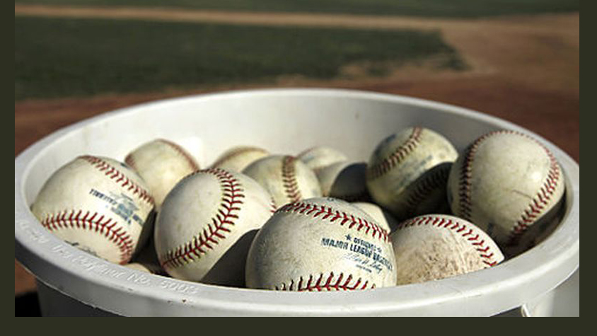MLB baseballs in a bowl on the playing field. photo by Charlie Riedel/AP