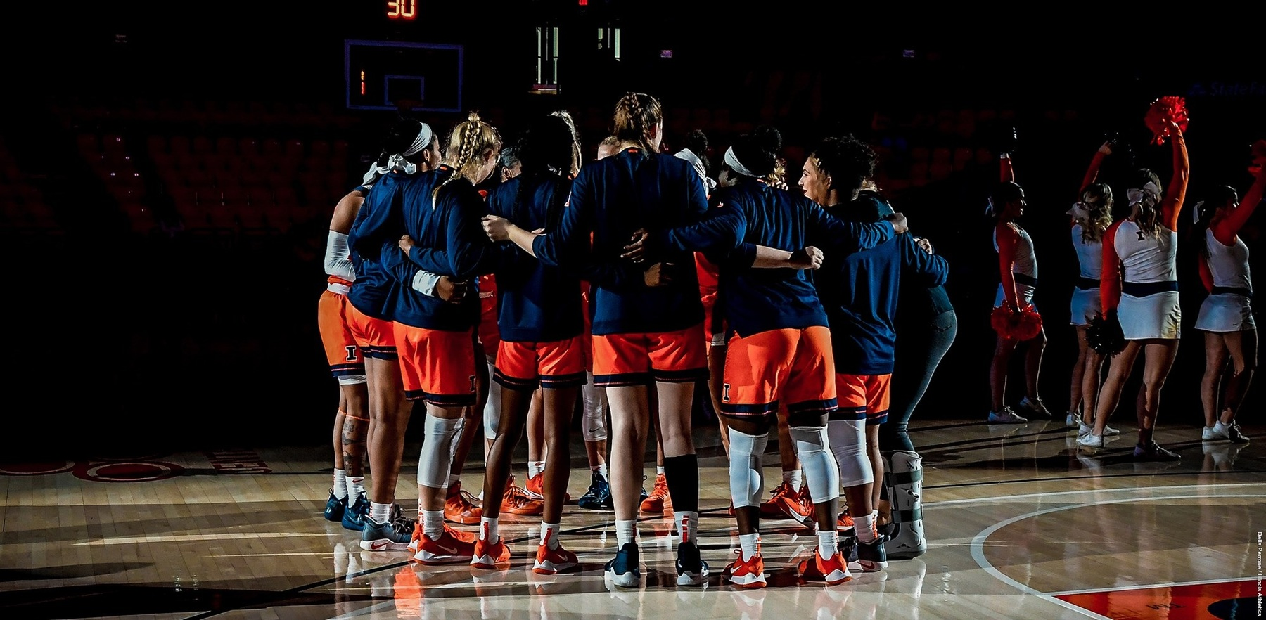 Illini players huddle in darkened gym during pregame introductions