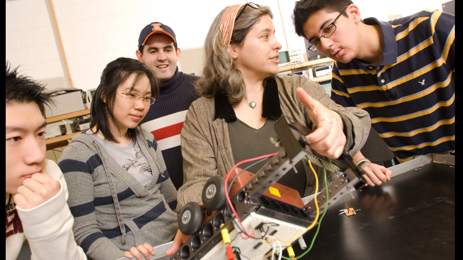 students and instructor inspect a robotic device