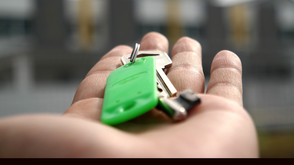 house keys on open palm, housing in background