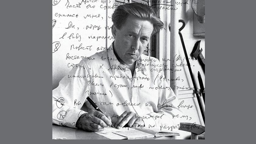 Solzhenitsyn writing at desk. Image from book cover