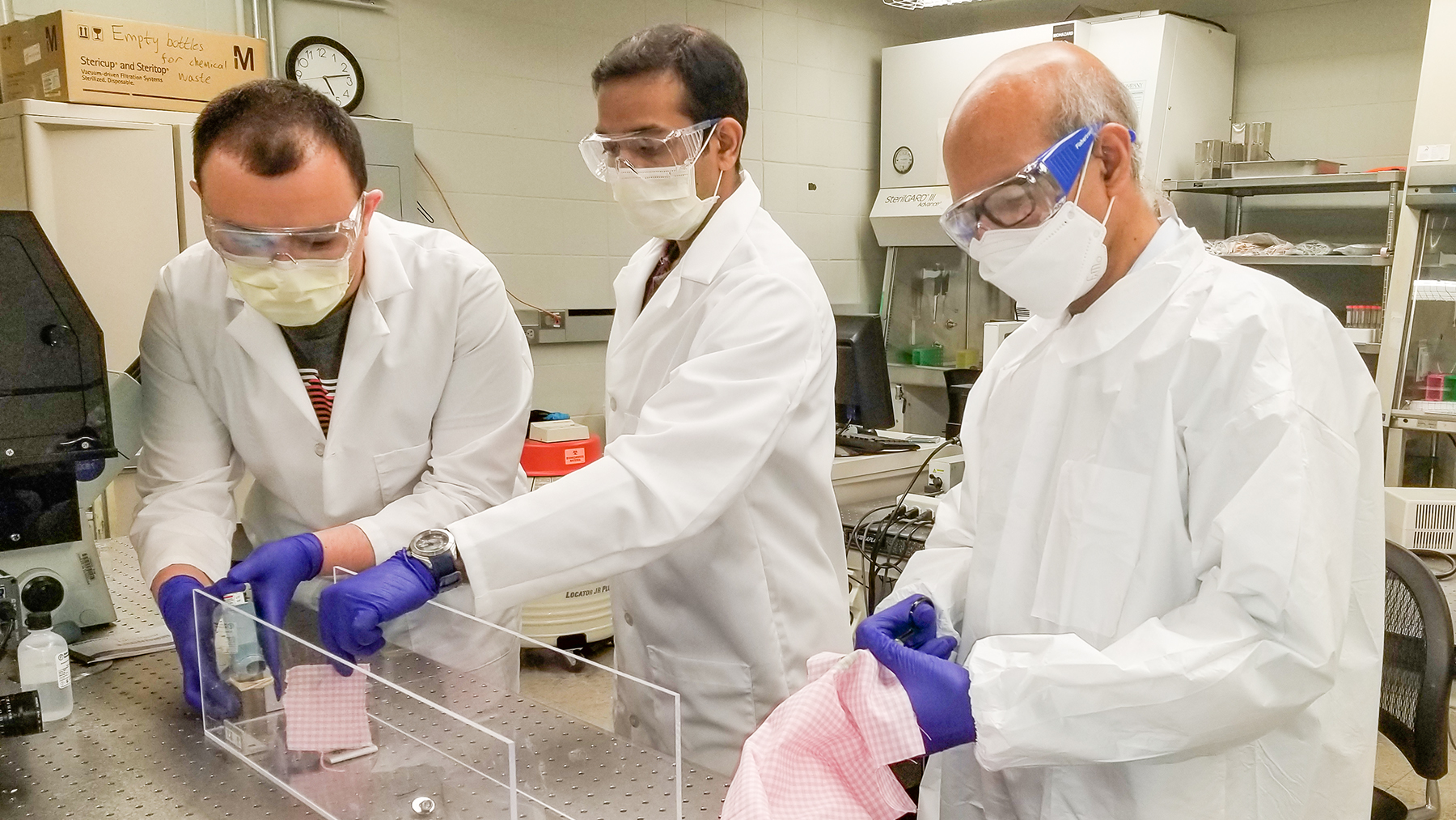 Mechanical science and engineering professor Taher Saif, right, and students Onur Aydin, left, and Bashar Emon test common household fabrics used to make face masks to help stop the spread of the coronavirus.