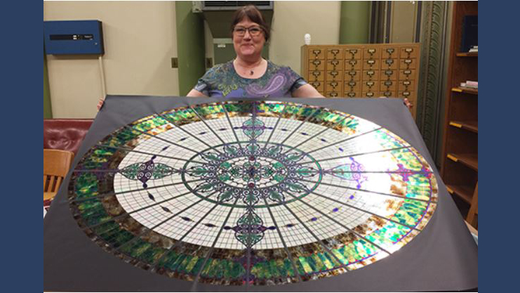 Jane Bergman poses with the foil replica of the former stained glass dome that once overlooked the Altgeld Hall library. (Photo courtesy of Jane Bergman.)