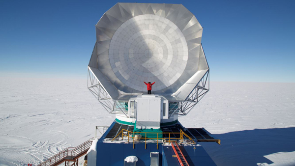 Andrew Nagolski stands beside a mocrowave telescope in Antarctica