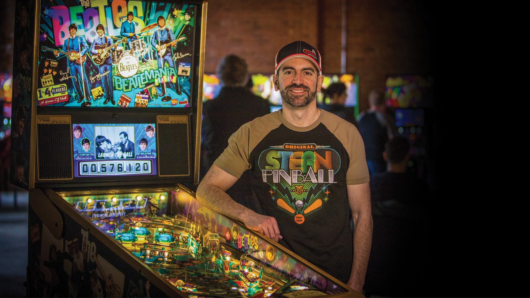 Zach Sharpe stands beside a 'Beatlemania'-themed pinball machine