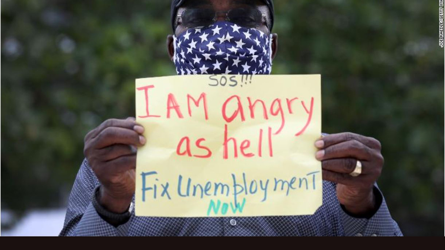 man with sign: 'Fix unemployment now.' photo via CNN