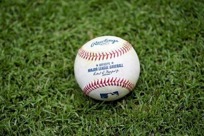 a Major League baseball sitting on grass