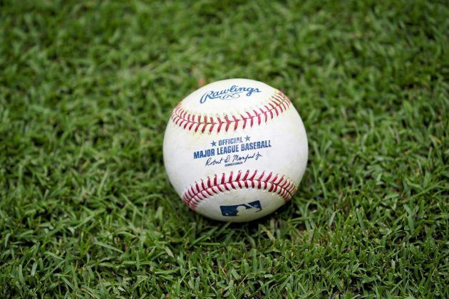 a Major League baseball sitting on grass