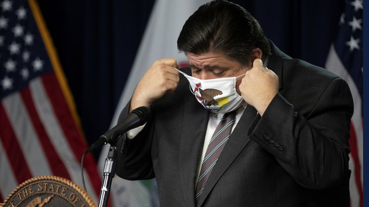 file photo of Governor J. B. Pritzker putting on a face covering