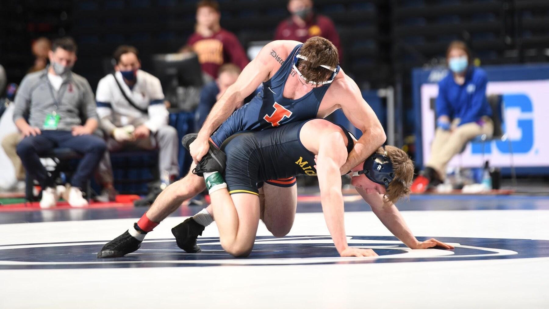 An Illini wrestler grapples with a Michigan wrestler