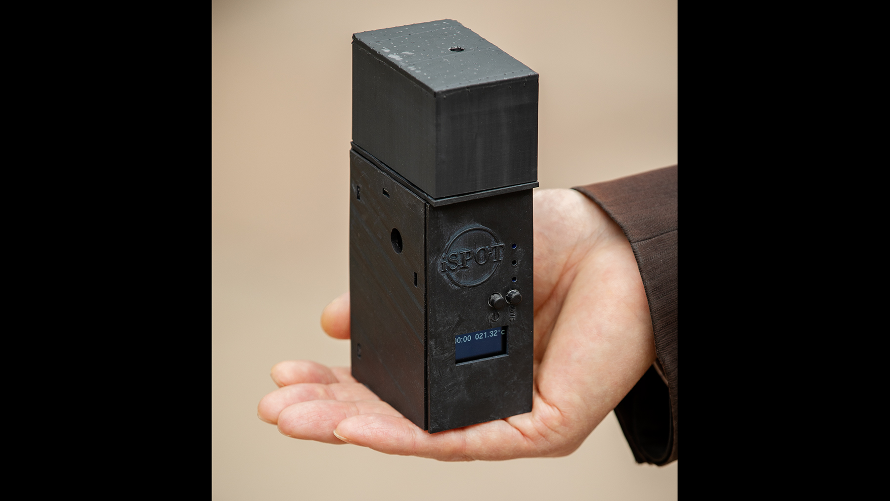 Photo of a hand holding a black rectangular testing device.