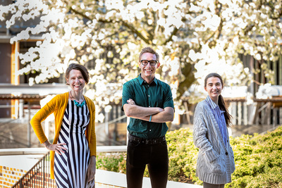 Portrait of three, smiling researchers standing outside with a white-flowering tree, bushes and a brick wall in the background.