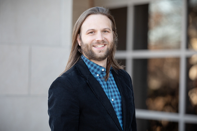 U. of I. graduate student Nathan Tanner standing outdoors next to a building's windows on the university campus