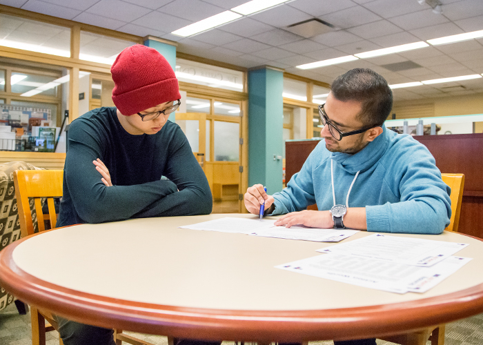 Yanchen Shi (left), a senior in bioengineering from Dunlap, Illinois, gets his resume reviewed at The Career Center by Rameez Siddiqui, a student paraprofessional there.