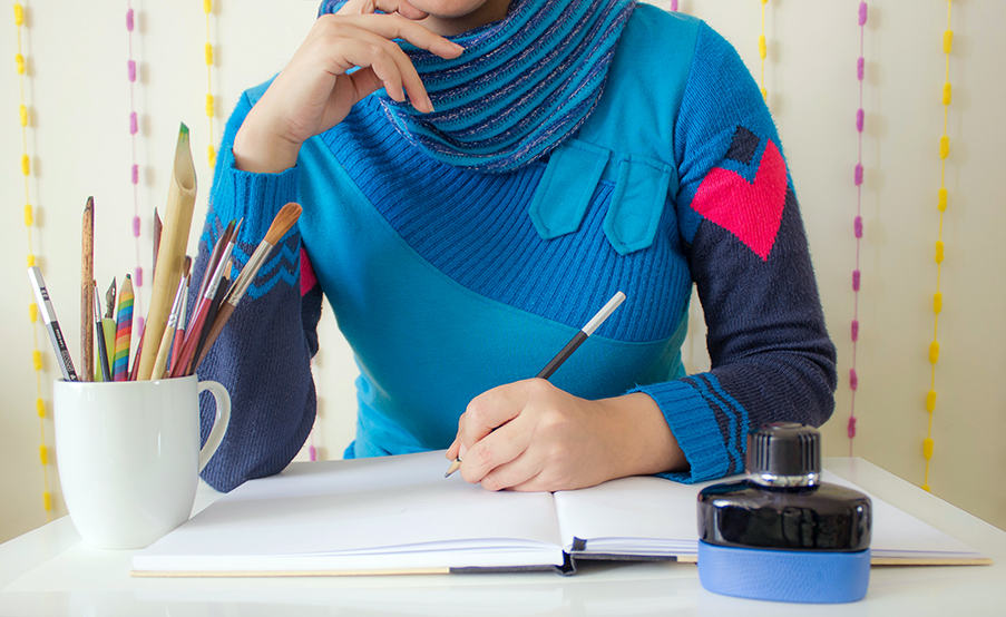 Person in blue sweater sits at desk with pens, paint brushes, and notebook ready to write something.