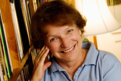 Headshot of Nina Baym next to books and with a lamp in background