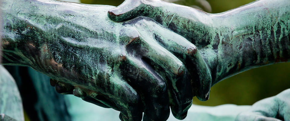 learning and labor statues shaking hands