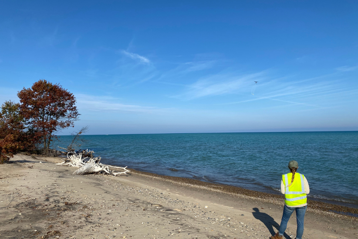 ISGS research technician Katie Braun flies a drone over Lake Michigan, collecting data by mapping magnetic materials both above and buried beneath the surface.