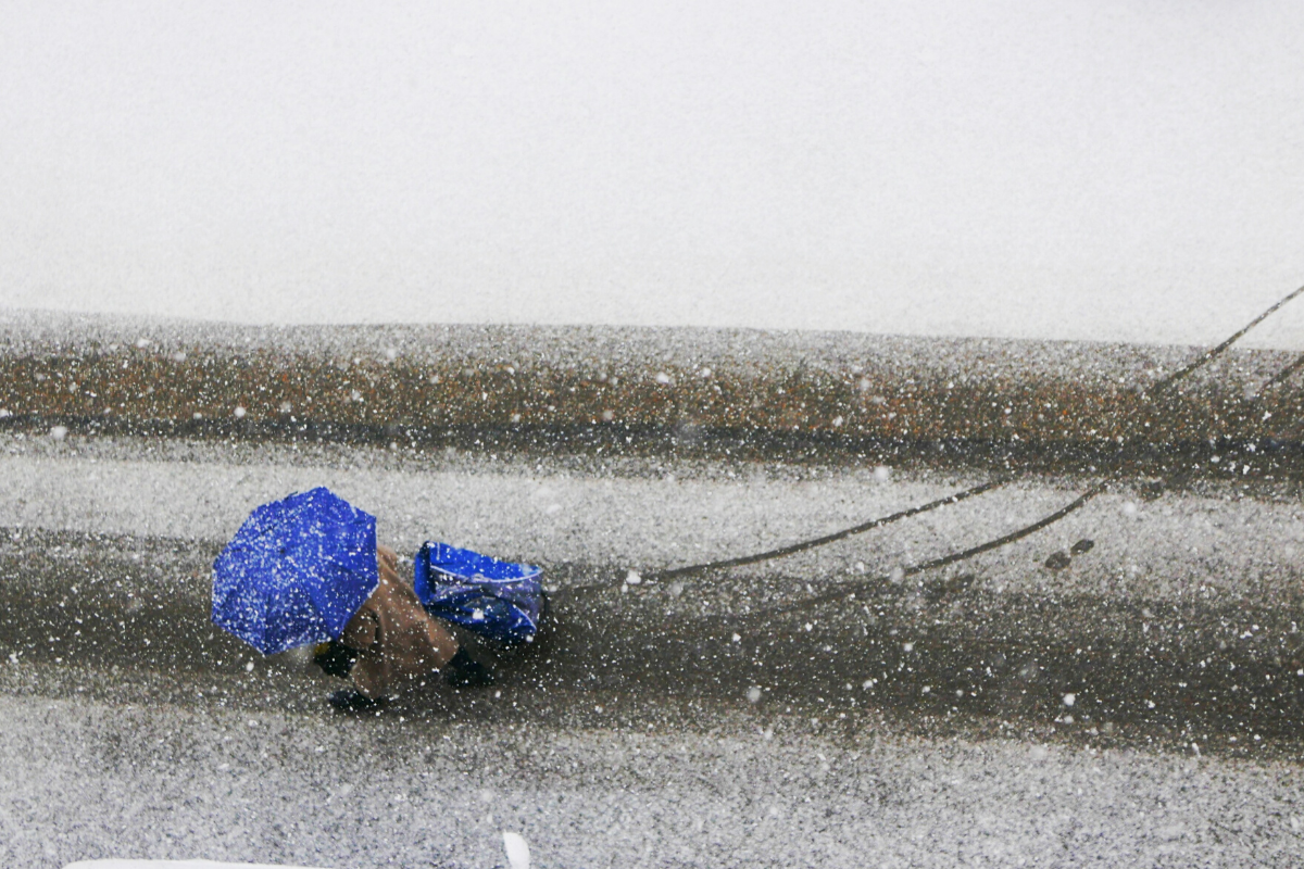 snow falling on person under umbrella