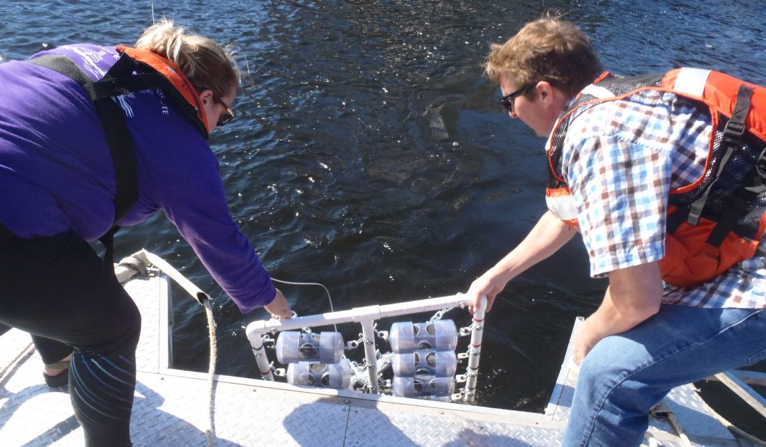 Maggie Oudsema and John Scott lower microplastic samples into Muskegon Lake